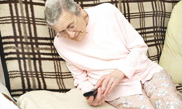 Picture shows an older woman looking at a mobile phone and pressing the keypad. NHS 111, the front door to the urgent care system, handles millions of calls a year but some question its usefulness.