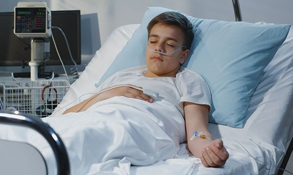 Picture shows a teenage boy lying in a hospital bed with his eyes closed.