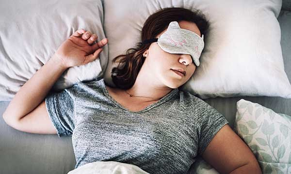A woman lying in bed asleep, wearing an eye mask to prevent sleep disturbance due to light levels