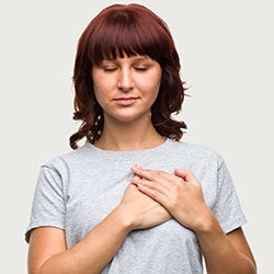 A woman trying to reduce anxiety by following a breathing exercise that starts with placing your hand on your heart and breathing deeply
