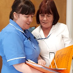 Ms Robinson with therapy assistant Kath Hopkin, reviewing a patient's medical notes
