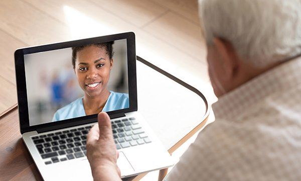 Primary care nurse carrying out a remote consultation via video on a laptop
