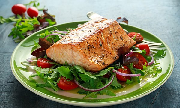 Picture shows a poached salmon fillet with vegetables. Oily fish are a rich source of vitamin D