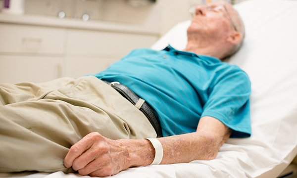 Picture shows frail older man lying on bed. Older people with frailty tend to present late and often in crisis at the emergency department