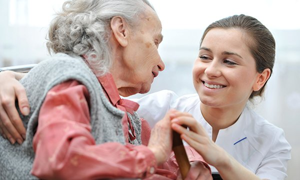 A care worker talking to a nursing home resident and holding her hand.  Care workers can start working towards a career as a registered nurse by undertaking a foundation course