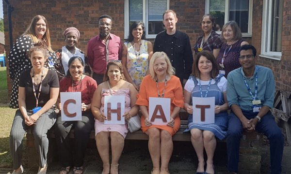 Clinical lead Melanie Pettitt with 12 fellow members of the award-winning Care Home Assessment Team in North London, four holding a CHAT sign