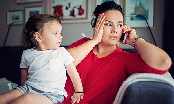 Picture shows mother on phone with child. Health visiting has been severely affected by COVID-19