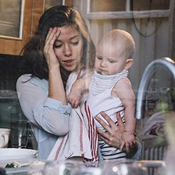 Picture shows strained mother at the kitchen sink with baby