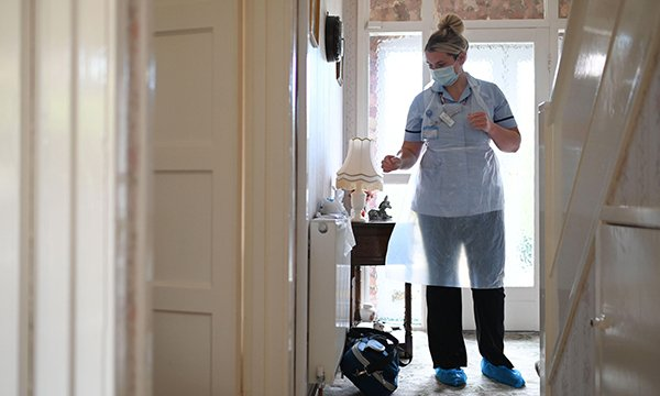 A nurse in PPE in the hallway of a patient's home