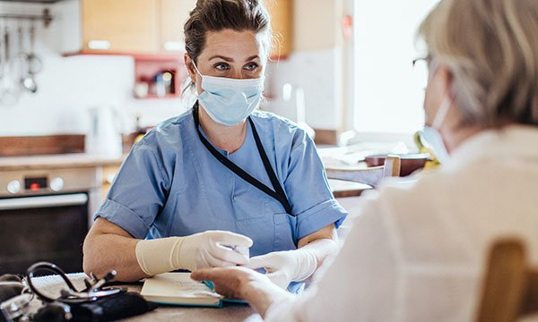 A healthcare worker wearing a mask and protective gloves talks to a female patient