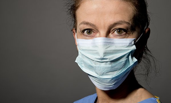 A nurse wearing a face mask and scrubs