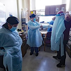 Hospital staff on a ward putting on PPE