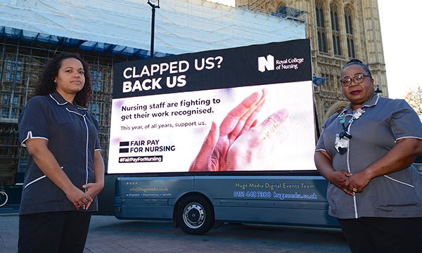 RCN members Grace Milner (left) and Kafeelat Adekunle with the new 'Clapped us? Back us' billboard