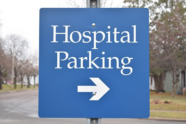Sign that reads 'hospital parking', with an arrow below