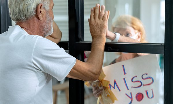 Picture shows an older couple separated by a window and holding their hands against the glass to greet each other