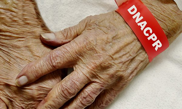 Image of an older person's hands with a 'Do not resusciate' notice placed on their wrist
