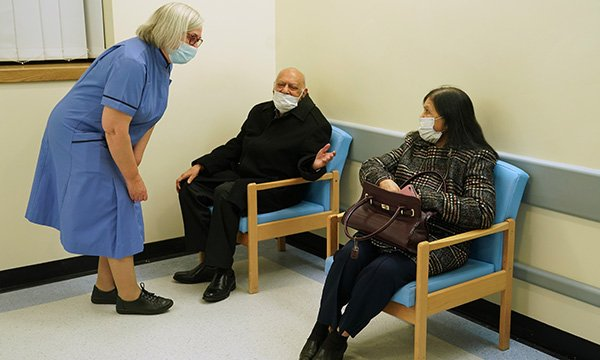Nurse wearing a facce mask talking to two patients in a clinic waiting room, both wearing masks
