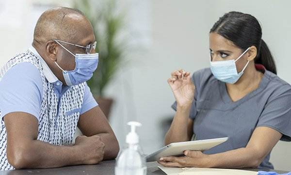 A Nurse talking to a BAME patient, both wearing face masks