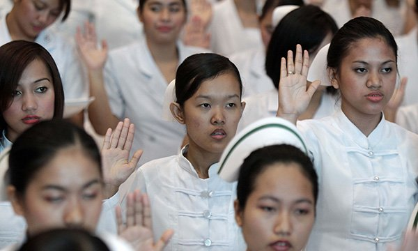 Graduate Filipino nurses during an oath-taking ceremony in the City of Pasay, Manila, Philippines, are part of the overseas cohort invited to join the UK temporary nurse register.