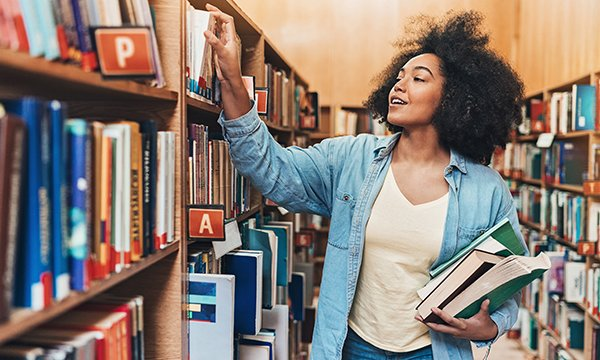 Woman choosing books out of a research library