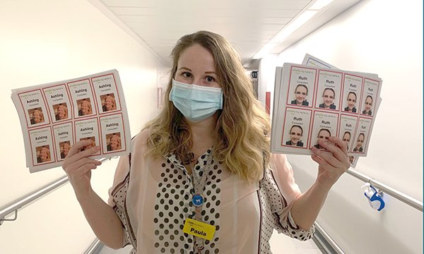 Paula Ryeland of Whittington Health holds staff picture badges designed to put patients at their ease during the coronavirus pandemic