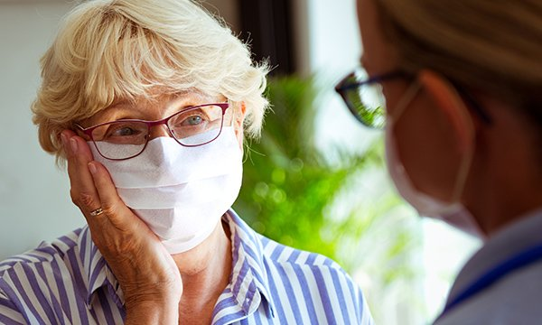 Masked older women talking to masked nurse
