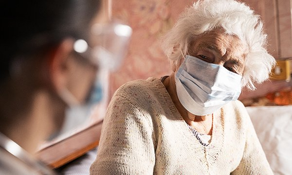 Picture shows nurse talking to a masked older woman