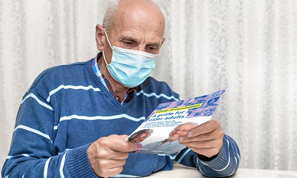 A patient reading information about the COVID-19 vaccination programme