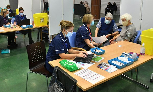 Nurses talk to patients about consent at the NHS vaccination centre at Epsom Downs Racecourse, Surrey