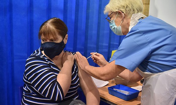 A woman receives the first of two Pfizer/BioNTech COVID-19 vaccine jabs at a vaccination centre in Cardiff, Wales