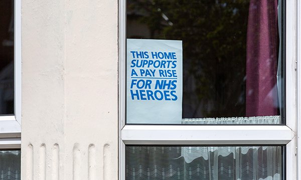 Poster in a window demonstrates public support for NHS pay rise