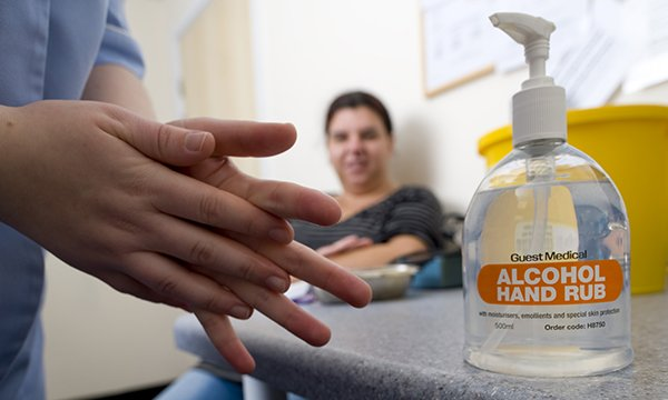 A person using alcohol hand gel