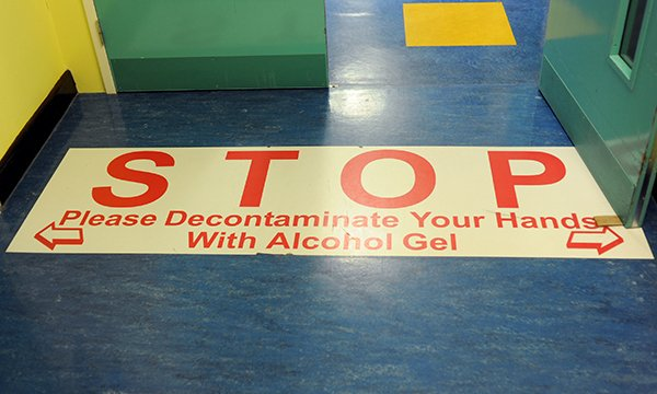 Sign on the floor in a hospital reminding people to use alcohol hand gel