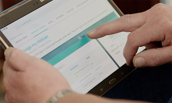 Picture shows a man's hand touching an electronic pad with the screen showing 'message to my physician'. New care pathways such as supported self-management are easing the strain on prostate cancer services.