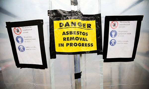 Picture shows a warning sign at the entrance of building undergoing asbestos removal