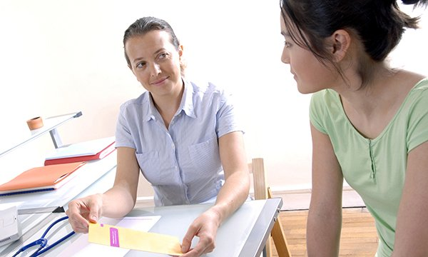 Picture shows a nurse talking to a young woman. Nurses can help dispel myths about the human papillomavirus, which can damage relationships and harm women's confidence and mental health.