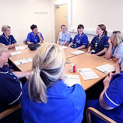 Picture shows nurses in a group discussion sitting around a table. In this article senior nurses discuss how to remove the culture of fear and create a compassionate workplace in which everyone feels valued.