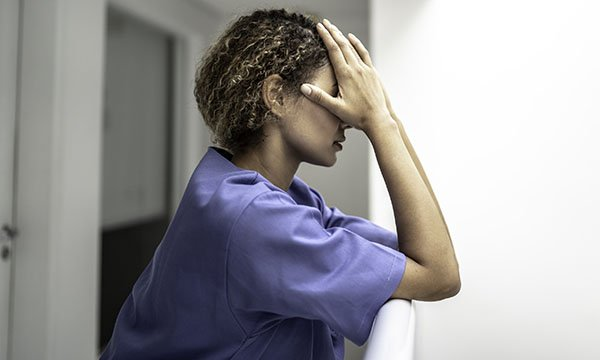 Picture shows a female medic holding her hands to her head in a gesture expressing stress or exhaustion