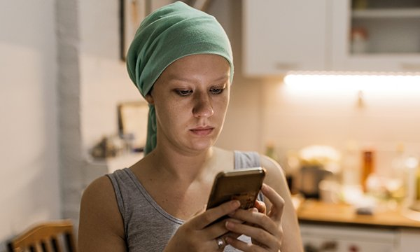 Picture shows a young woman wearing a headscarf after radiation therapy looking pensive as she uses her phone. A self-help app called Untire can help cancer patients and survivors regain their energy.