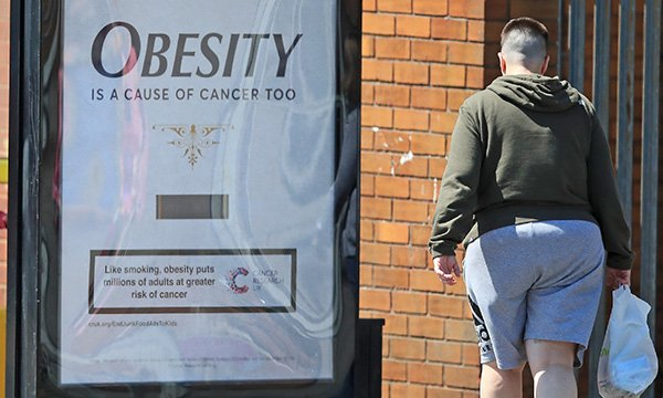 Someone looking at an besity causes cancer campaign poster