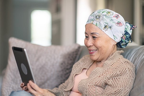 Picture shows an older woman, who is wearing a scarf to hide her hair loss from chemotherapy, using a tablet to message friends and family. Talking about their lived experience gives people affected by cancer a chance to work through their feelings.