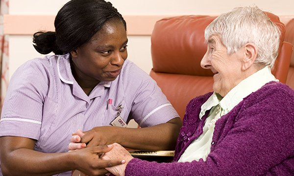 Picture shows a healthcare assistant with a care home resident. The pay of social care staff, including nurses, must be raised to help stabilise the sector in England, a health charity says