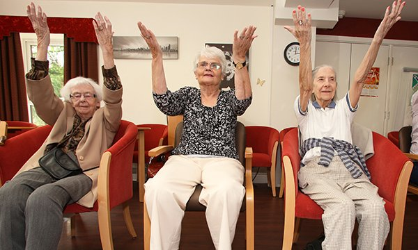 Picture shows three older women sitting in chairs with their arms raised in a group exercise session. A four-year project will build data resource on treatment and services at care homes.