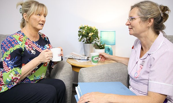 Picture shows a woman chatting to a medic, who is holding some folders. Care planning discussions about the wishes of people with dementia, including whether to attempt CPR, should be proactive due to its inevitable progression.