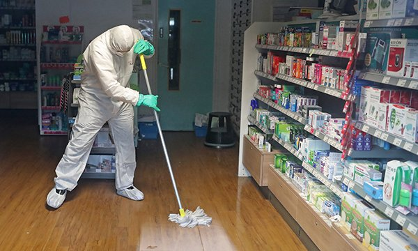 A worker in protective clothing cleaning the County Oak Medical Centre in Brighton