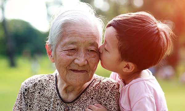Picture shows a child kissing an older Asian woman. This article is by academics conducting a research project on what can be learned from care of older people in different cultures.