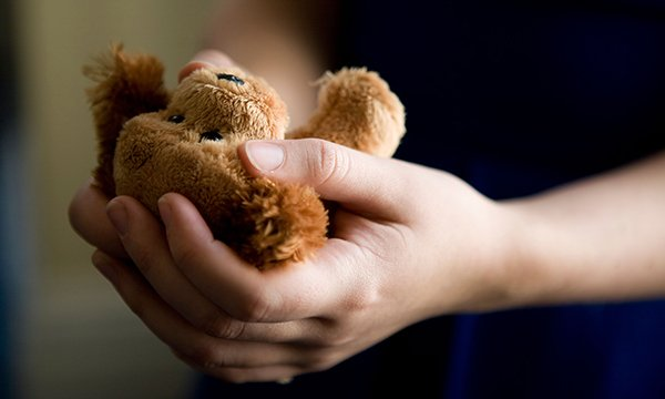 Image shows adult hand holding child's toy. A paediatric emergency department sister has written Guidelines for the Care and Transfer of the Deceased Child in the Emergency Department and organised Study Days to give staff skills and confidence to cope.