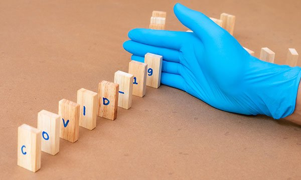 Picture shows a row of dominoes spelling out COVID-19