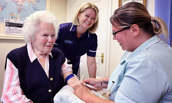 Practice nurse manager Emma Williamson oversees healthcare assistant Victoria Larkman as she takes a blood sample. Ms Williamson studied her practice's leg ulcer care and devised a pathway that improved healing, reduced spending and freed nurses' time.