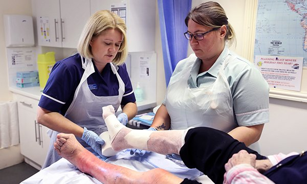 Practice nurse manager Emma Williamson and healthcare assistant Victoria Larkman treating a patient. Ms Williamson studied her practice's leg ulcer care and devised a pathway that improved healing, reduced spending on dressings and freed up nurses' time.